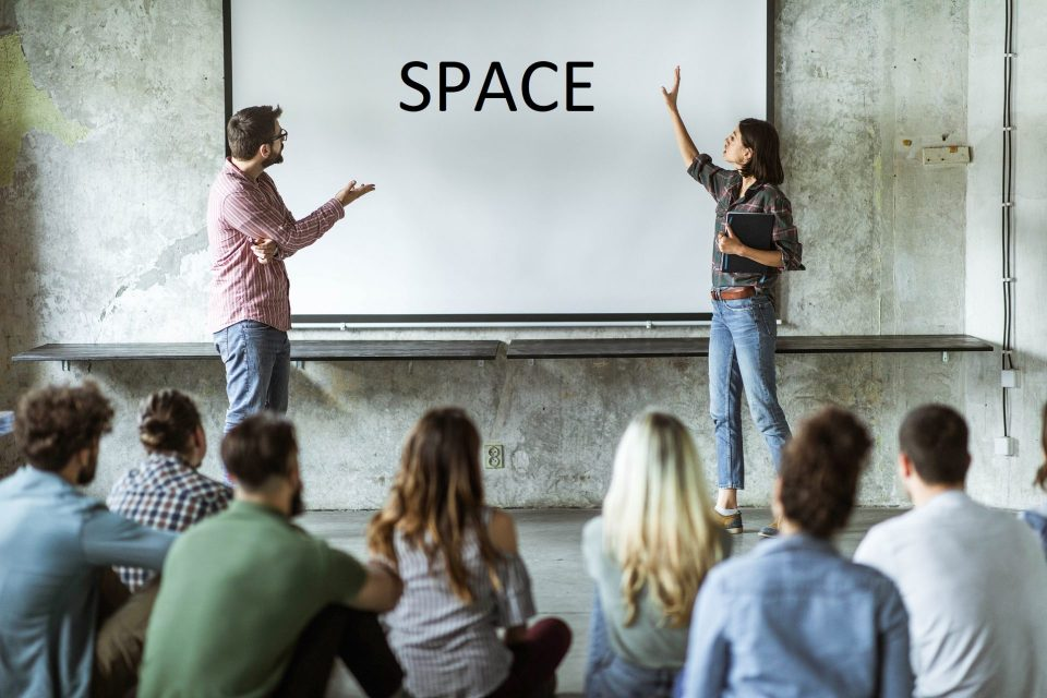Two presenters point to the word SPACE