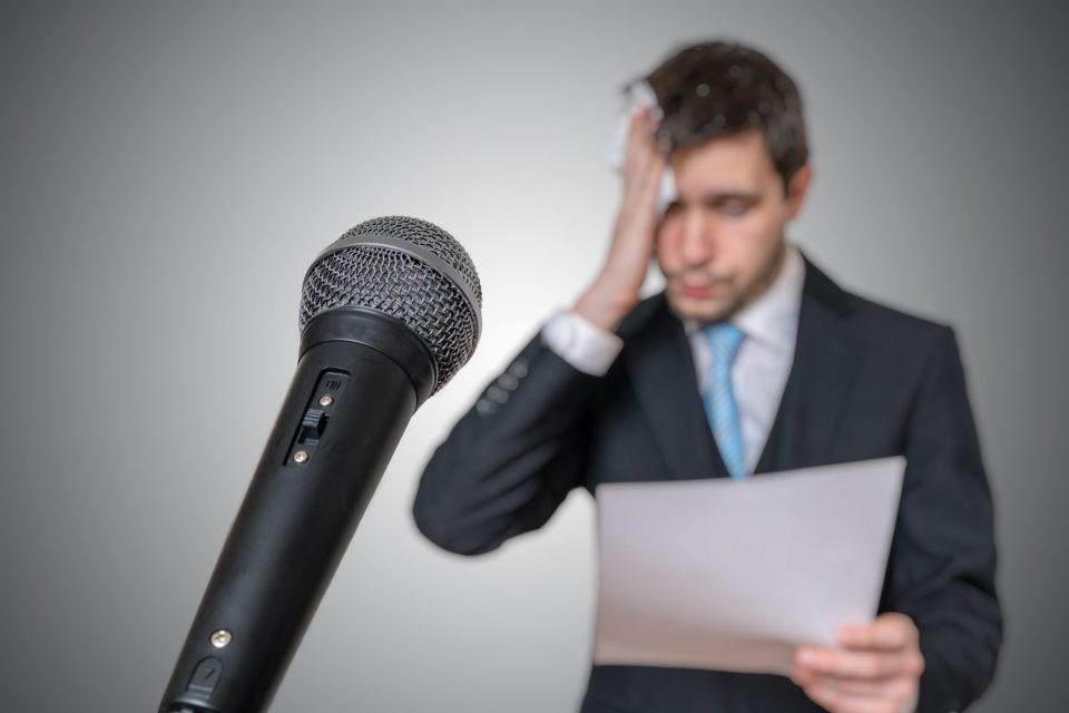 Nervous man is afraid of public speech and sweating. Microphone in front
