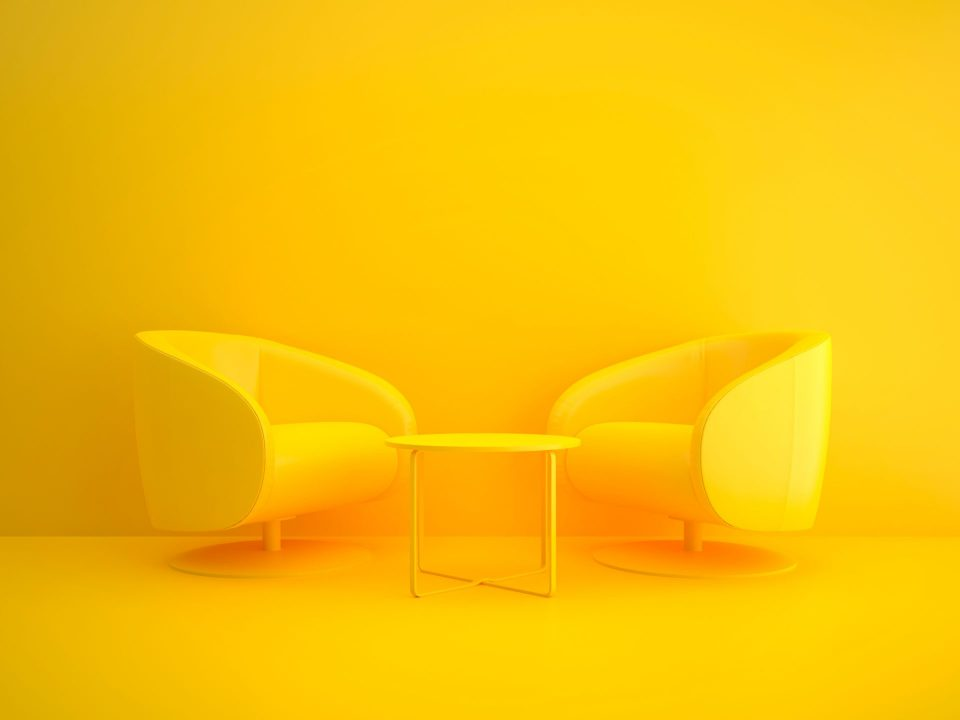 Two yellow chairs and table on yellow background
