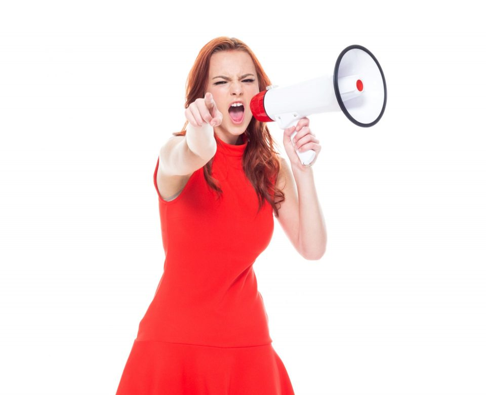 woman in red dress pointing while holding megaphone