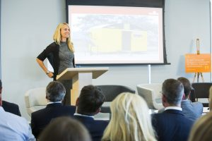 woman presenting behind lecturn