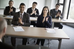 Business colleagues clapping hands in learning seminar office classroom