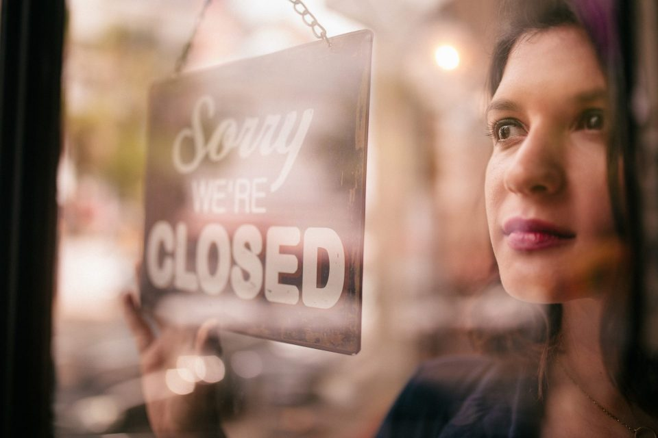 business owner facing closed sign