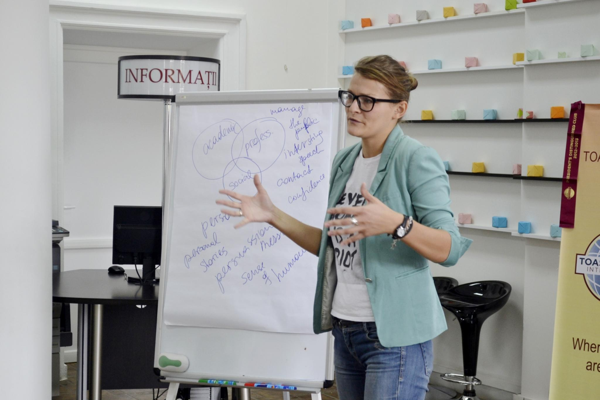 lady speaking standing next to a flip chart