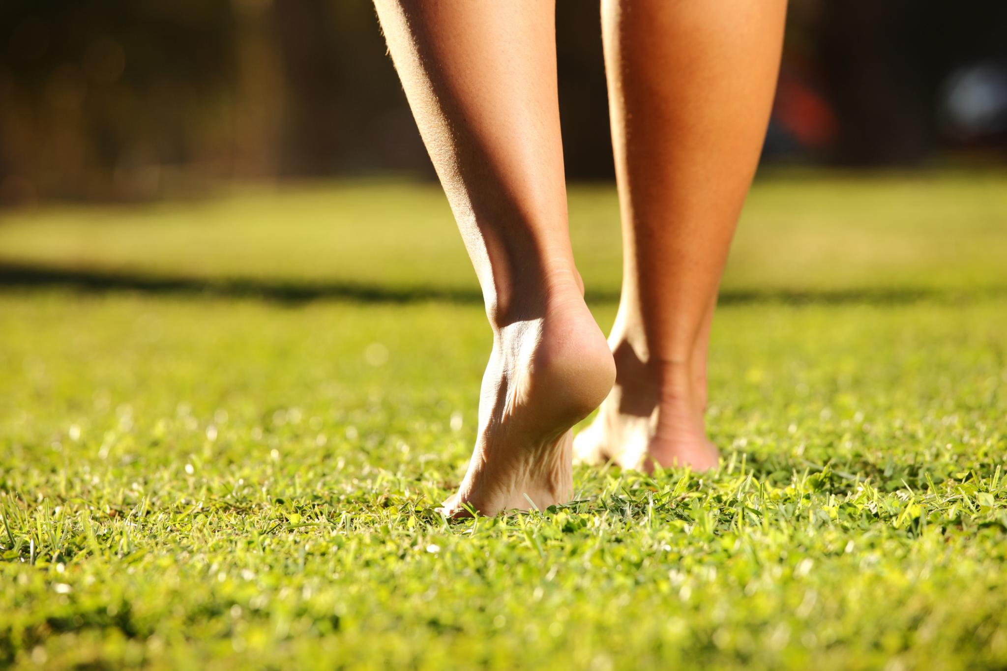 Lady walking barefoot on grass
