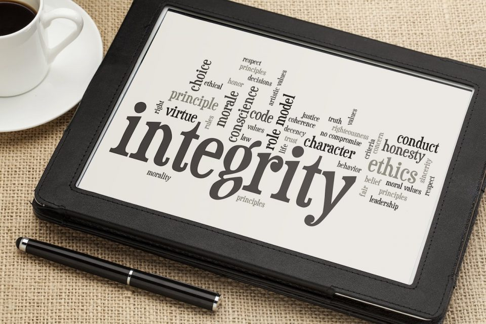 The word integrity on screen with pen