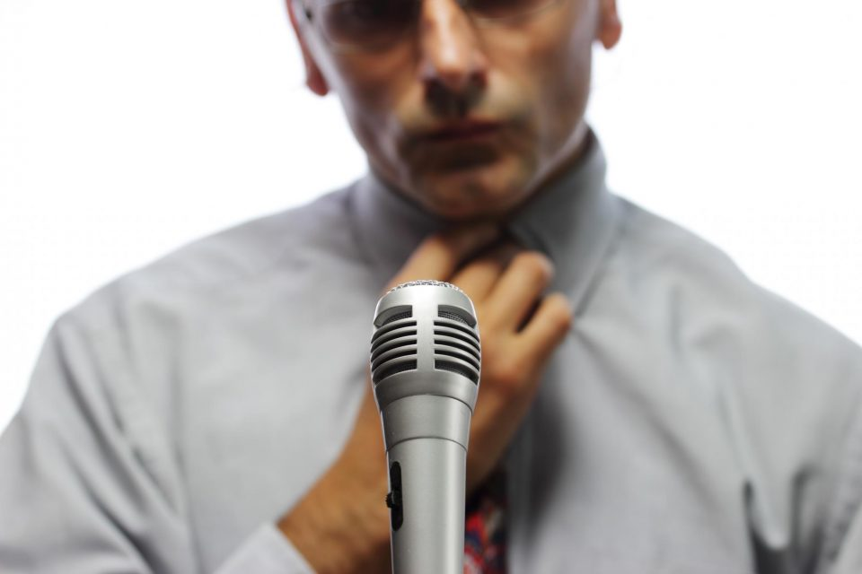 man looking nervous in front of microphone