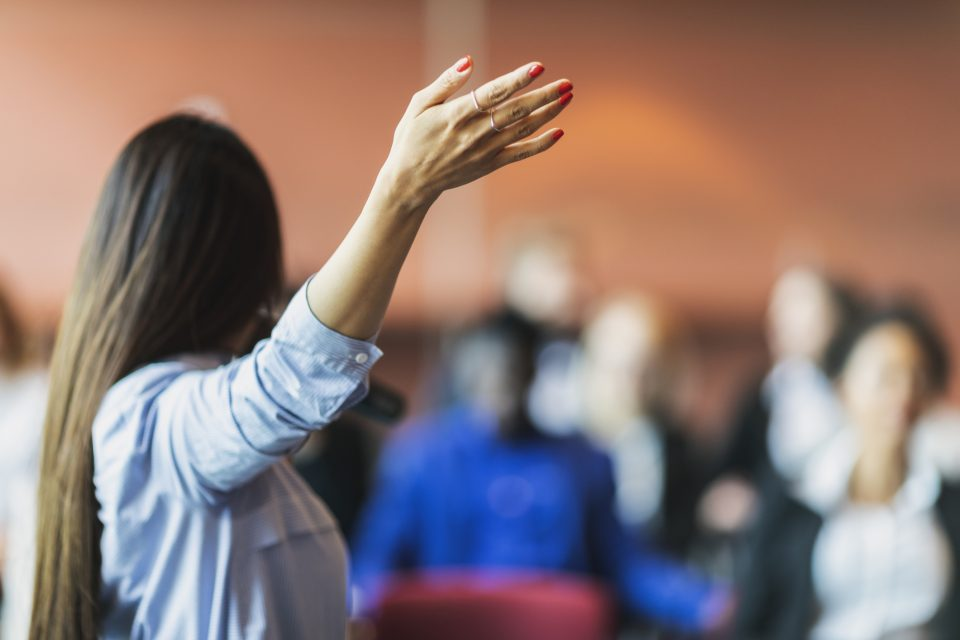 A female presenter interacting with the audience at a business presentation in the board room. Focus on her hand