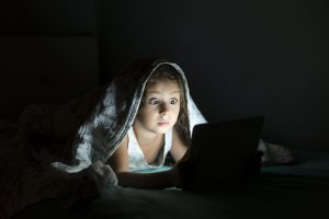 girl reading story under blanket on tablet