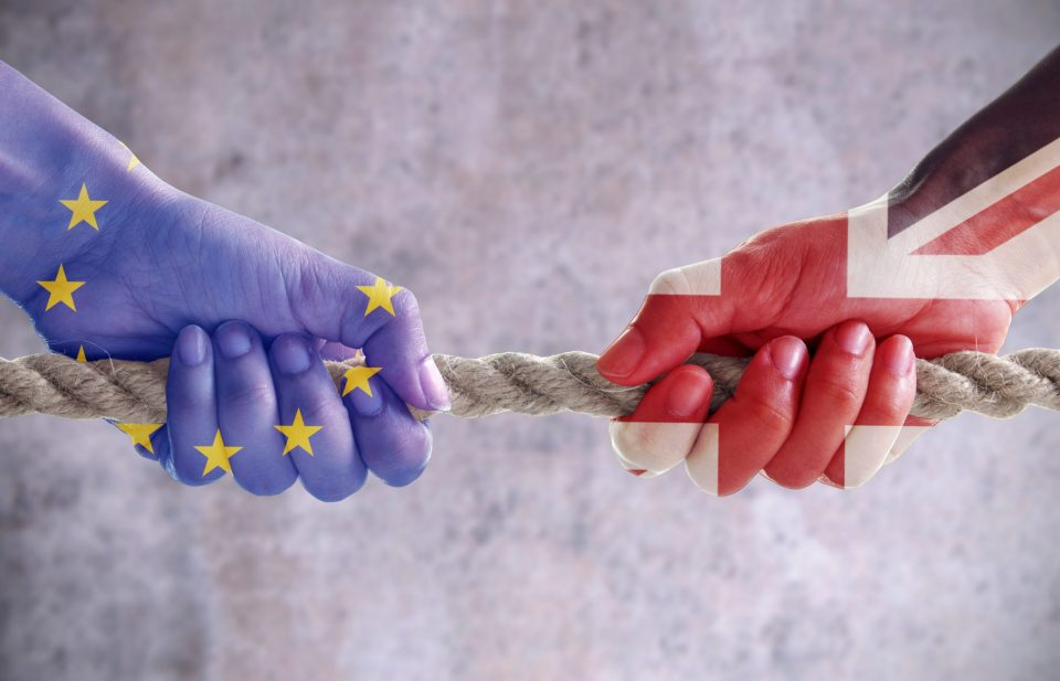 Tug of war between hands painted with UK and European flags