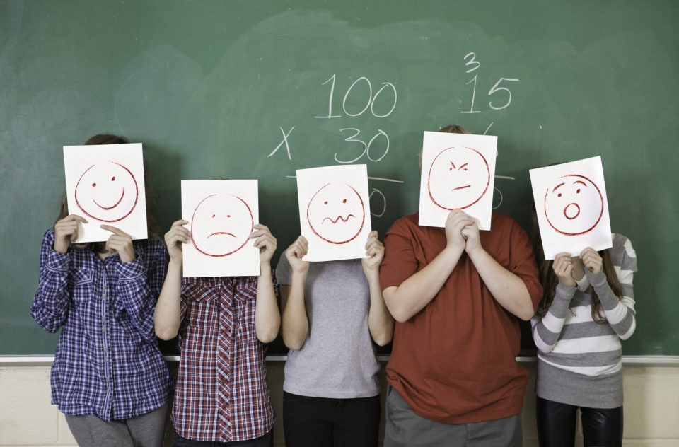 Five students holding faces of different emotions they have from worry to happy