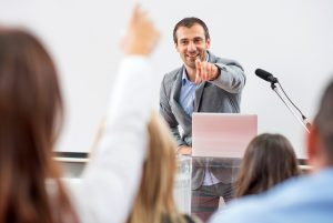 presenter pointing to audience member with hand up