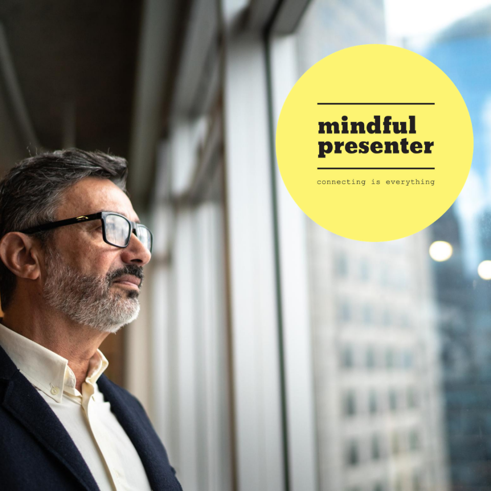Business man looking out of window at mindful presenter logo
