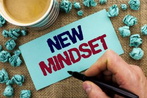 Writing note showing New Mindset. Business photo showcasing Attitude Latest Concept Vision Behaviour Plan Thinking written by Man Holding Pen Sticky Note Paper the jute background Cup