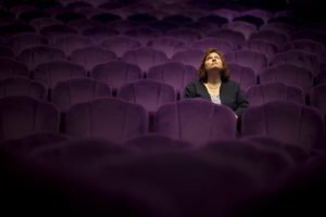 a woman sitting in the theater - she looks up - selctive focus on women
