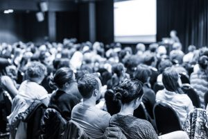 speaker and audience at a conference - black and white image